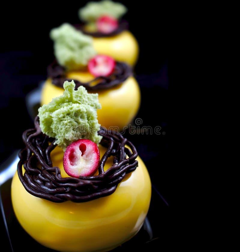 Desserts jaunes avec l'éponge et les canneberges vertes de pistache photo stock