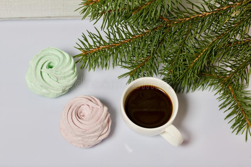 Desserts for winter parties. Sweets and spruce branch. Marshmallows and a cup of coffee. Desserts for winter parties. Sweets spruce branch stock images