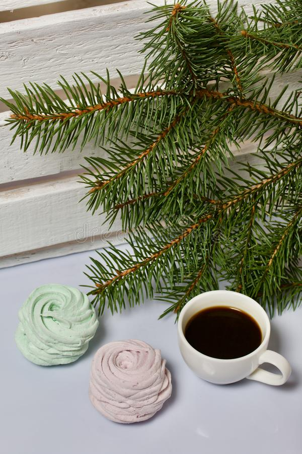 Desserts for winter parties. Sweets and spruce branch. Marshmallows and a cup of coffee. Desserts for winter parties. Sweets spruce branch royalty free stock photography