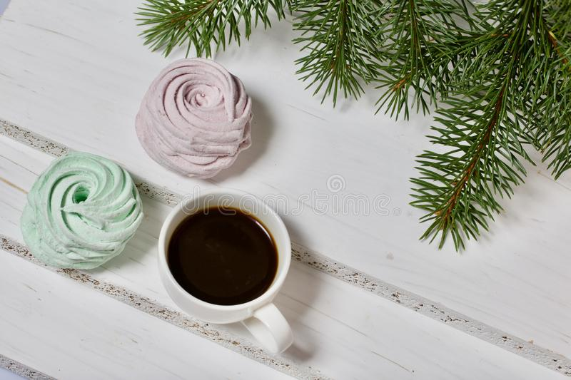 Desserts for winter parties. Sweets and spruce branch. Marshmallows and a cup of coffee. Desserts for winter parties. Sweets spruce branch stock photos