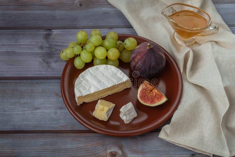Dessertvoorgerechten aan wijn - fig., Briekaas, rode druiven, honing dienden op een ceramische plaat op een zwarte hoogste mening stock fotografie