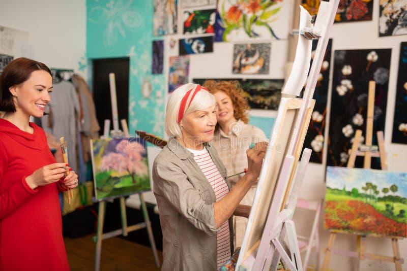 Dessin âgé de professeur d'art se tenant près de ses étudiants photo stock