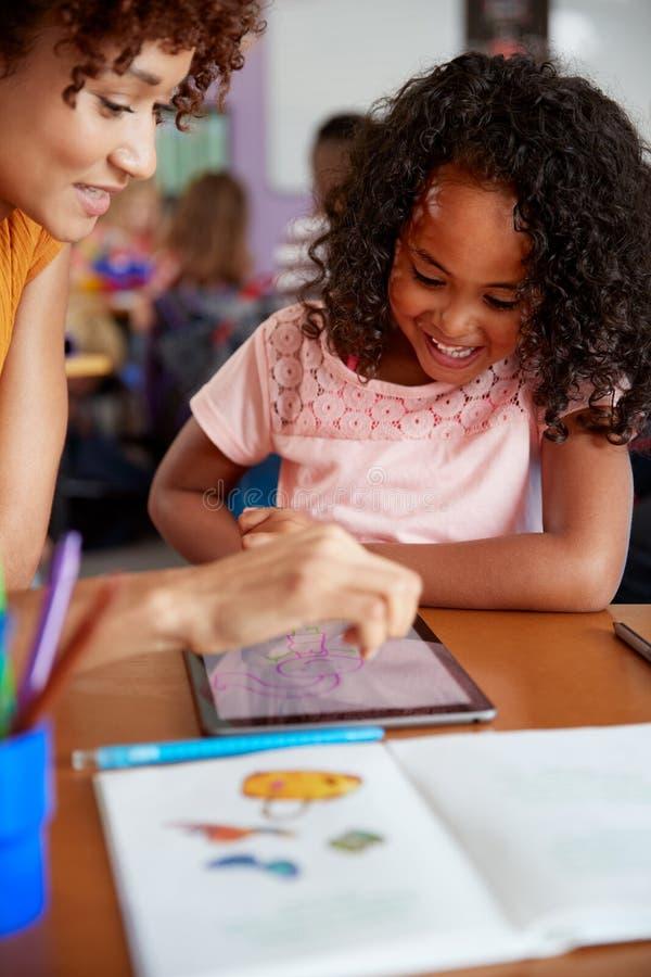 Dessin élémentaire d'And Female Pupil de maître d'école utilisant la Tablette de Digital dans la salle de classe images libres de droits