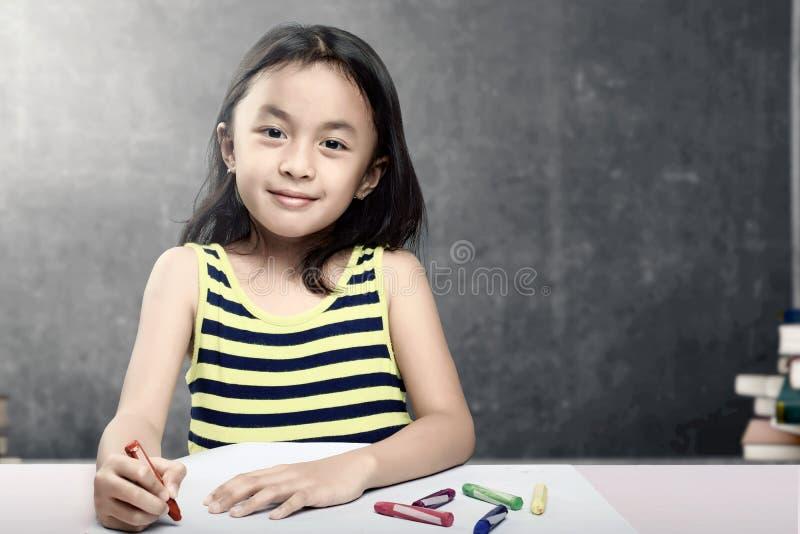 Dessin asiatique de fille d'?tudiant sur le livre blanc avec les crayons color?s dans la salle de classe avec des piles des livre images libres de droits