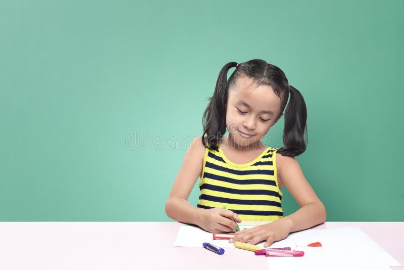 Dessin asiatique mignon de petite fille avec le crayon tout en se reposant au tabl photos libres de droits