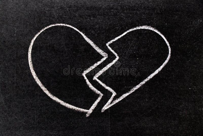 Dessin blanc de main de craie dans la forme du coeur brisé sur le tableau noir photographie stock libre de droits
