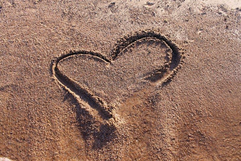 Dessin d'un coeur sur la plage images libres de droits