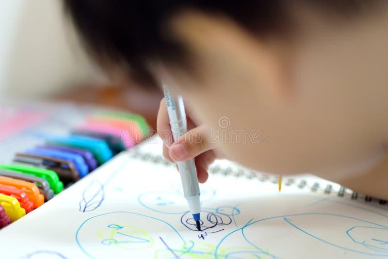 Dessin de bébé de plan rapproché avec le stylo de couleur photographie stock