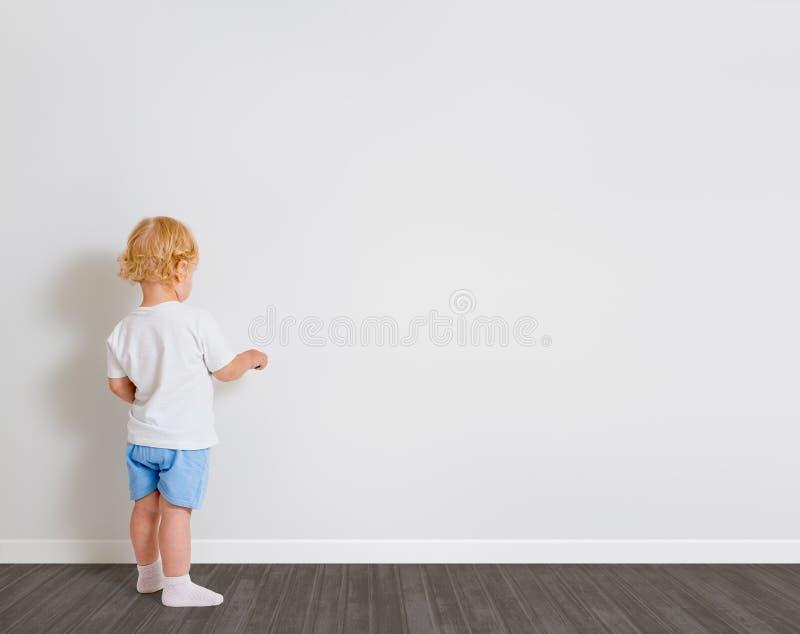 Dessin de bébé garçon sur la position de papier peint de nouveau à la caméra photo stock