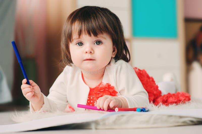 Dessin de 1 an de bébé avec des crayons à la maison photographie stock libre de droits