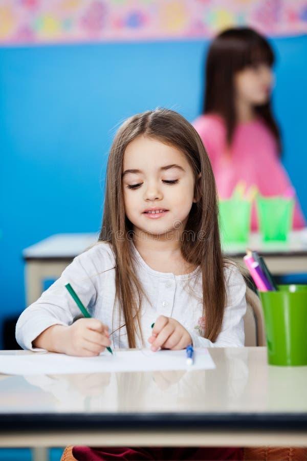 Dessin de fille avec le croquis Pen In Preschool image stock