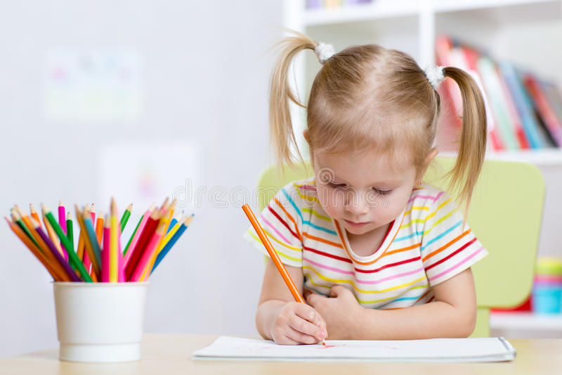 Dessin de fille d'enfant avec les crayons colorés dans la crèche photos libres de droits