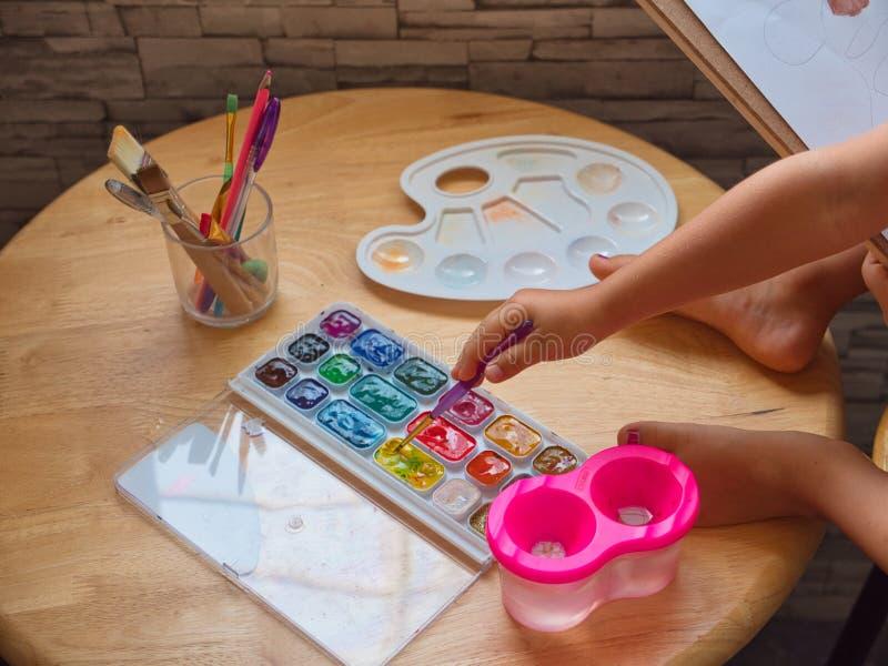 Dessin de fille d'enfant par l'aquarelle à la maison photos libres de droits