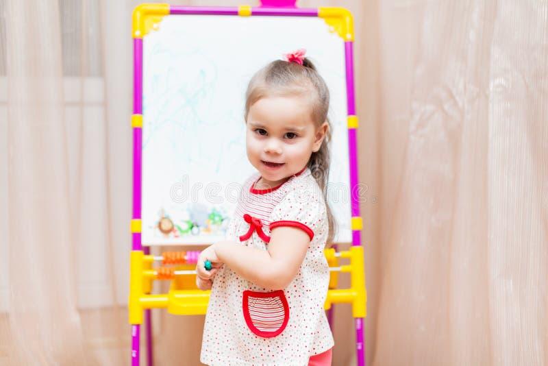 Dessin de fille d'enfant sur le conseil blanc image stock