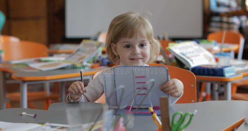 Dessin de fille ? la table dans la salle de classe ?ducation Enfant s'asseyant ? un bureau photographie stock libre de droits