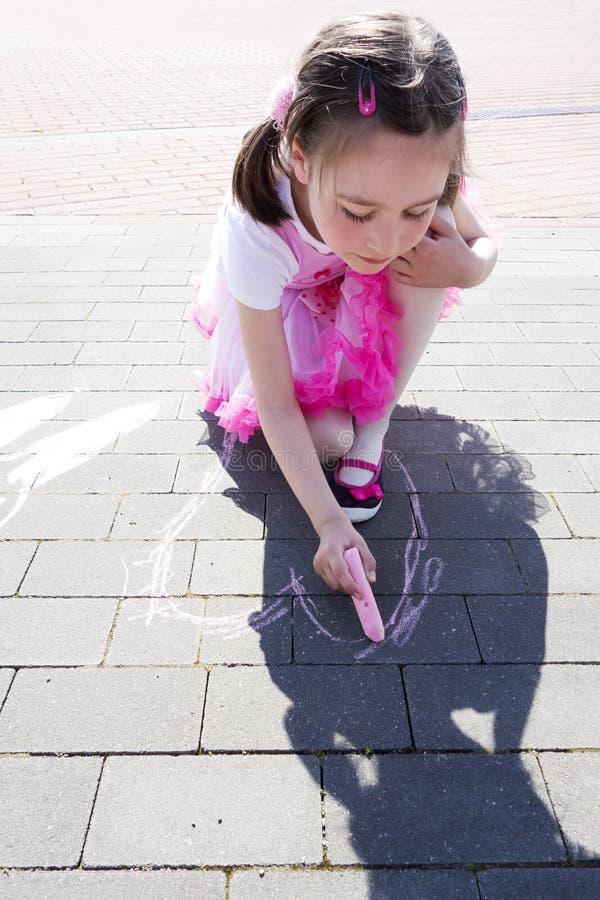 Dessin de fille sur le trottoir avec la craie photo libre de droits
