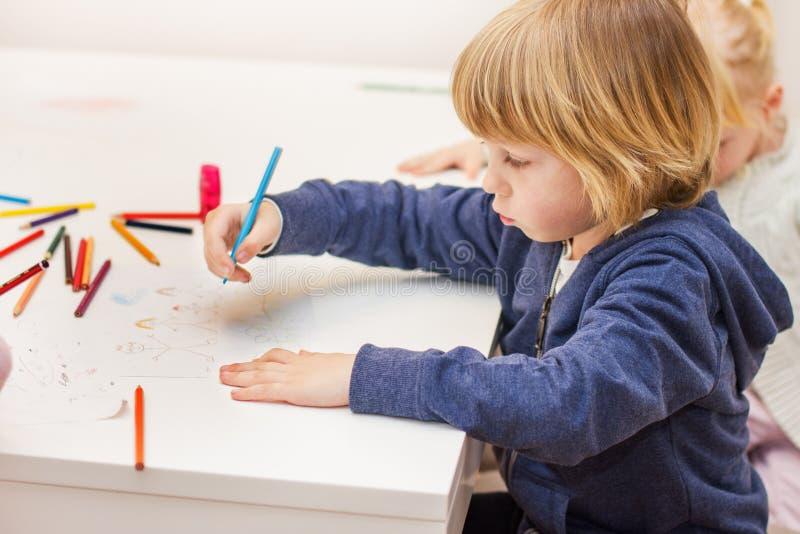Dessin de garçon avec les crayons colorés photographie stock