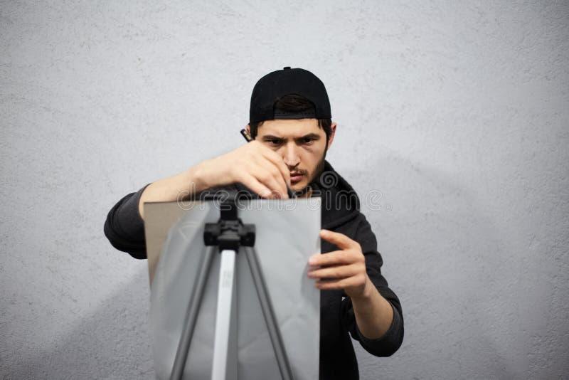 Dessin de jeune homme avec le crayon dans des ses mains photo stock