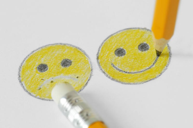 Dessin de visage souriant avec l'expression positive et négative avec le crayon et en caoutchouc - concept de positivité photos libres de droits