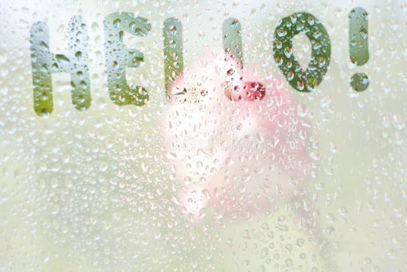 dessin en forme de doigt des rayures du mot bonjour sur le verre embrumé translucide gouttes de pluie de pluie de ressort sur la  photo libre de droits