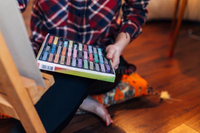 Dessin femelle d'artiste avec la craie en pastel sur la toile d'eagel Studio confortable photo stock