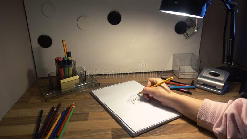 Dessin femelle de main sur une feuille de papier avec un crayon 4k images libres de droits