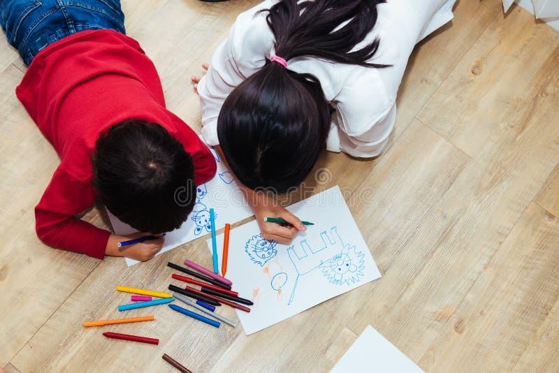 Dessin heureux de peinture de jardin d'enfants de gar?on et de fille d'enfant de groupe d'enfants de famille de vue sup?rieure su image libre de droits