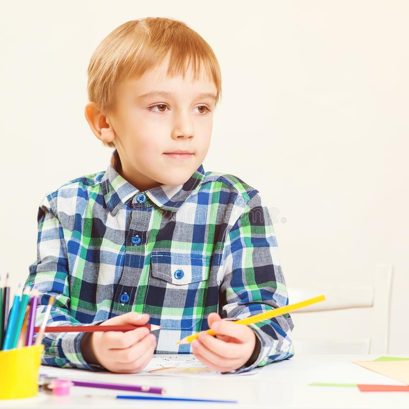 Dessin heureux de petit garçon avec les crayons colorés Petit dessin mignon d'enfant d'élève du cours préparatoire à la classe Cl images libres de droits