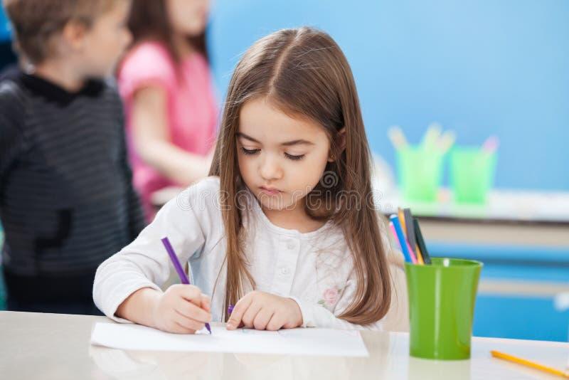 Dessin mignon de fille avec le croquis Pen In Classroom photo libre de droits
