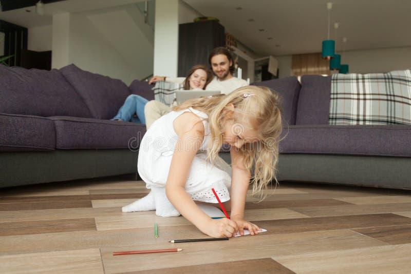 Dessin mignon de fille de fille avec les crayons colorés jouant à la maison photos libres de droits