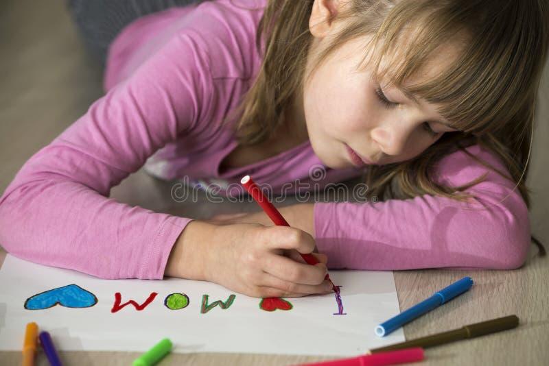 Dessin mignon de fille d'enfant avec les crayons color?s j'aime la maman sur le livre blanc ?ducation artistique, concept de cr?a photo libre de droits