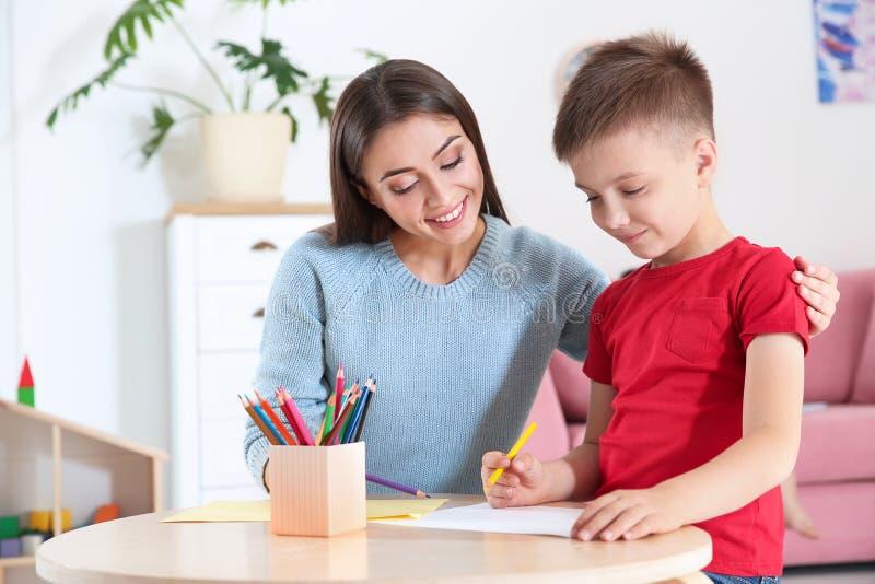 Dessin mignon de petit enfant à la table avec sa mère photographie stock libre de droits