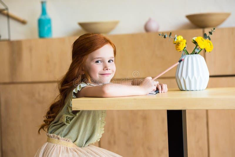dessin roux adorable de fille avec le crayon et sourire à l'appareil-photo tout en se reposant à la table images stock