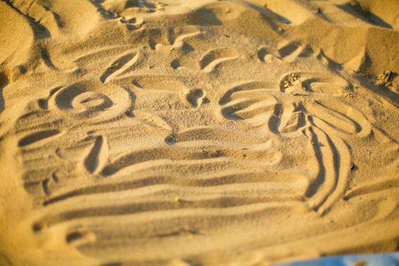 Dessin sur le sable fait par un plan rapproché d'enfant photos stock