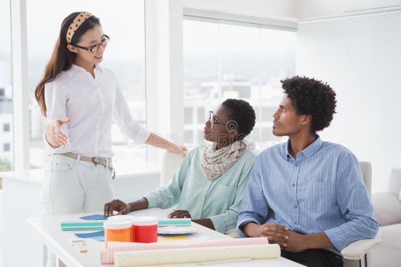 Dessinateur d'intérieurs parlant avec des clients photos stock