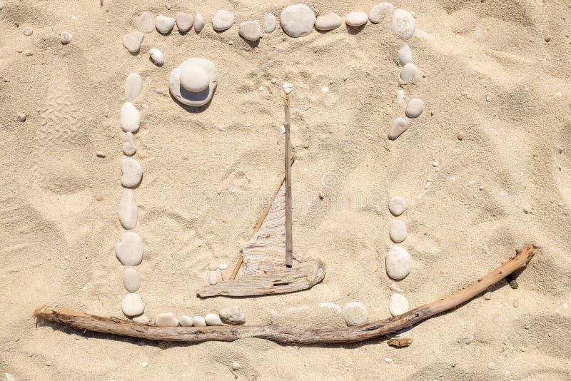 Dessins artistiques de sable sur la plage avec des cailloux et le sti en bois photo libre de droits