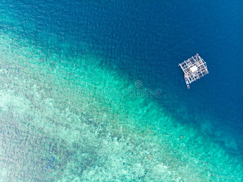 Dessus aérien en bas du bateau de pêche traditionnel de vue flottant sur la mer des Caraïbes tropicale de récif coralien de turqu image libre de droits