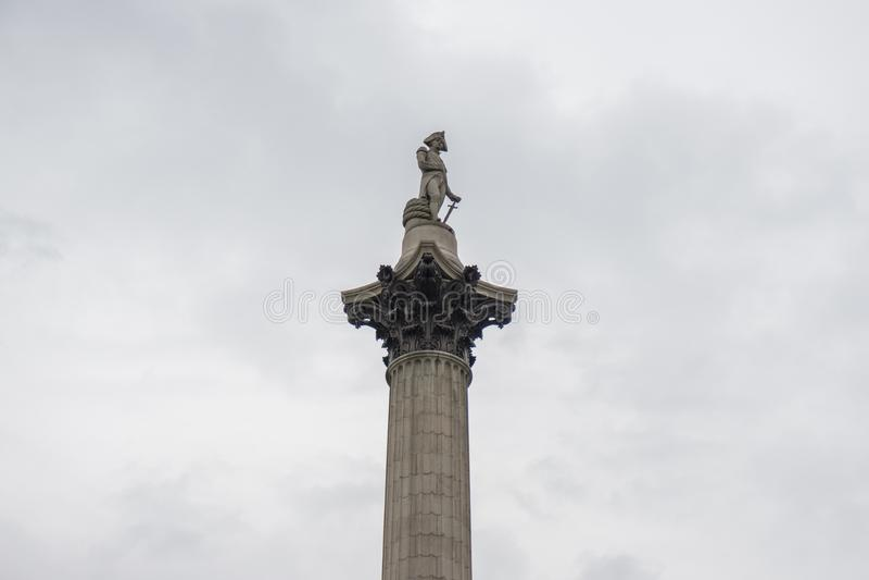 Dessus de colonne du ` s du Nelson dans Trafalgar Square, Londres contre un ciel obscurci gris photos stock