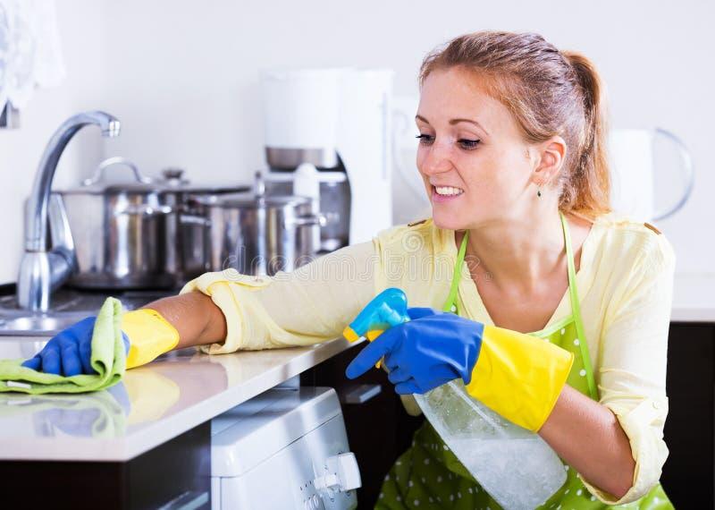 Dessus de cuisine de saupoudrage de femme à la maison photo libre de droits
