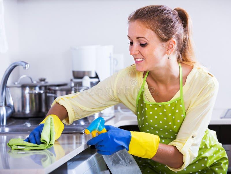 Dessus de cuisine de saupoudrage de femme à la maison image stock