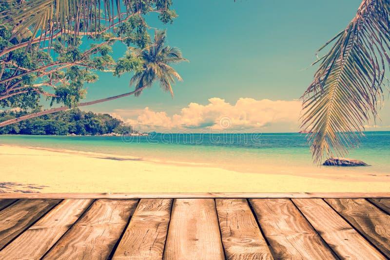 Dessus de la table en bois sur la mer brouillée avec le fond d'arbre de noix de coco, processus de vintage photographie stock