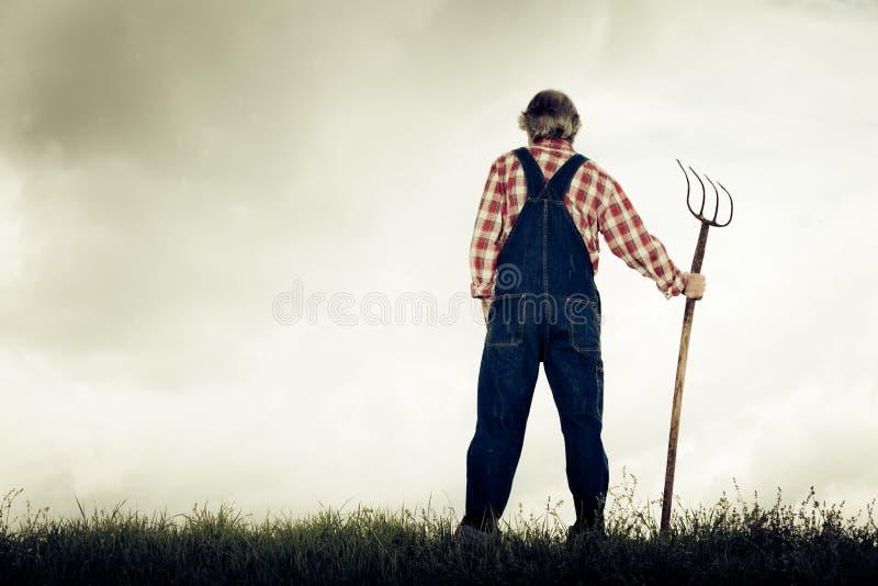 Dessus de Standing At The d'agriculteur d'une colline photo stock