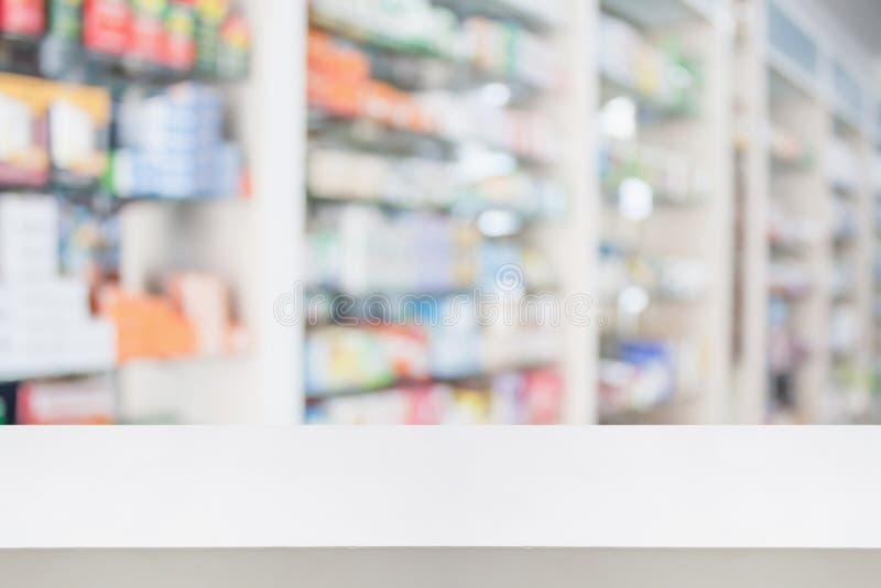 Dessus de table de compteur de magasin de pharmacie avec la médecine de tache floue sur des étagères photos stock