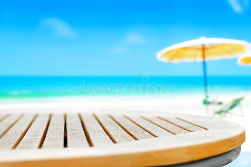 Dessus de table de grume sur le fond de plage de tache floue photo libre de droits