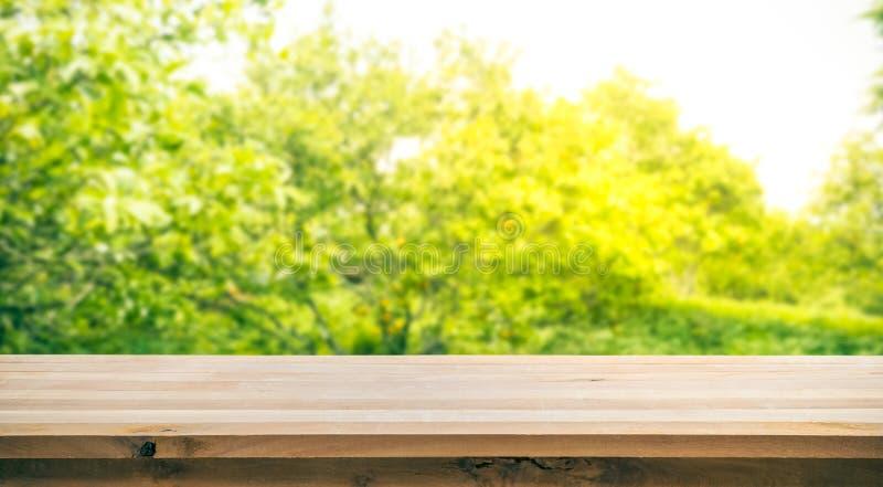 Dessus de table en bois avec la tache floue du jardin orange pendant le matin photographie stock