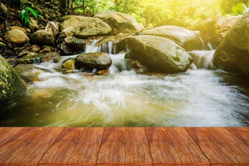Dessus de table en bois sur la cascade naturelle de tache floue avec la lumière du soleil image stock