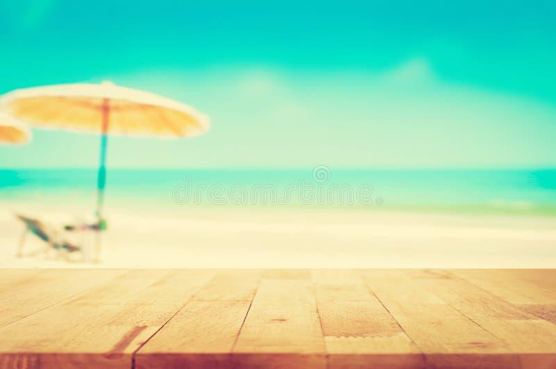 Dessus de table en bois sur la mer bleue brouillée et le fond blanc de plage de sable, ton de vintage photos libres de droits