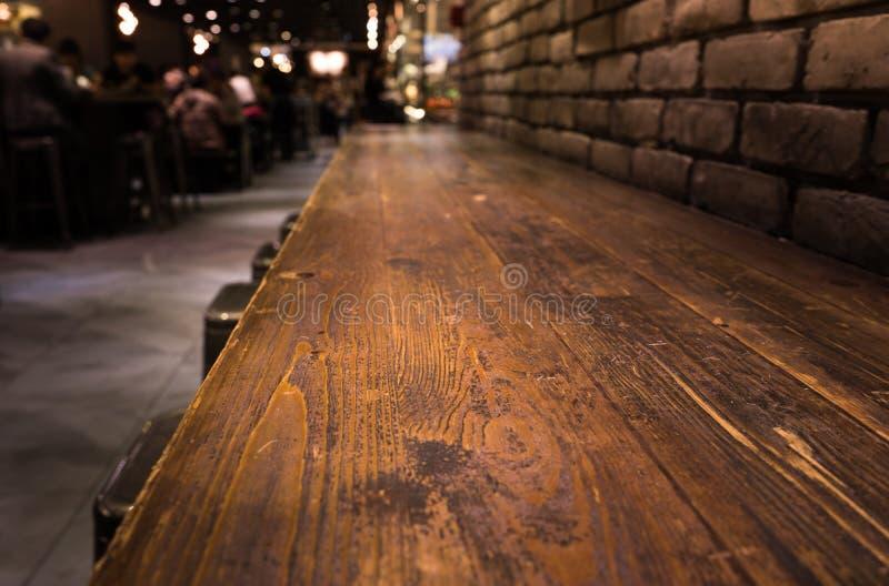 Dessus de table en bois vide de barre avec la tache floue du restaurant de café dans l'obscurité images stock