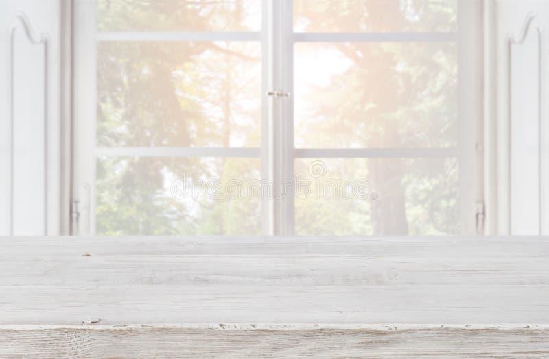 Dessus de table en bois vide sur le fond brouillé de la fenêtre de vintage images stock
