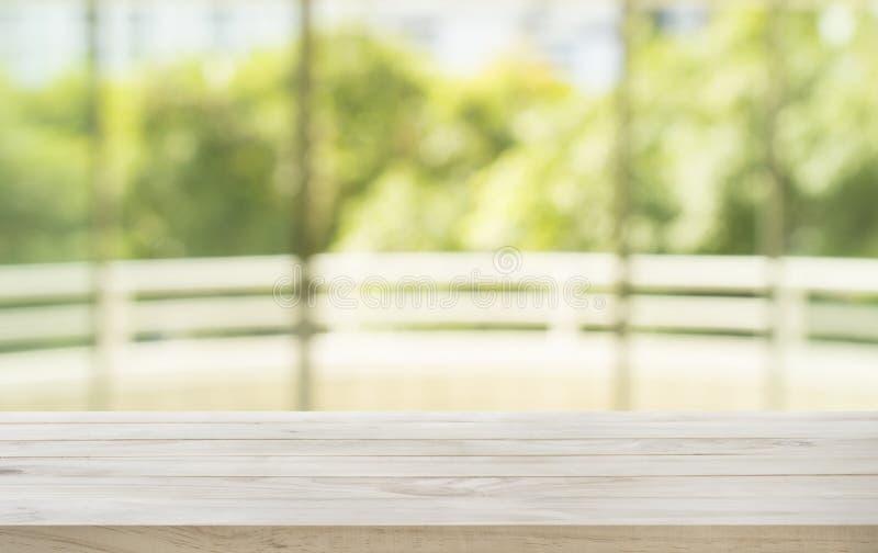 Dessus de table en bois vide sur le jardin de vert d'abrégé sur tache floue de la fenêtre photo stock